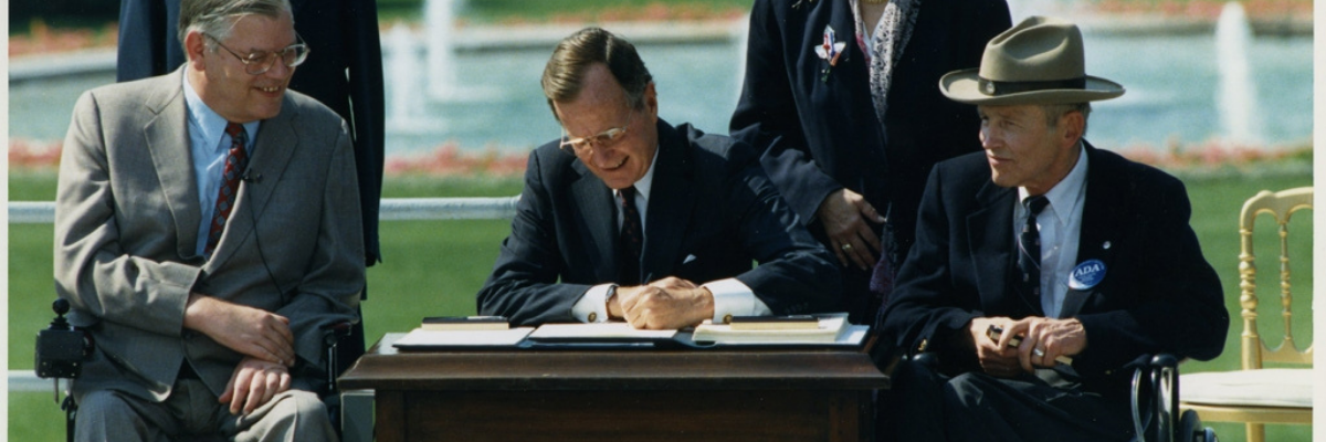 Photo of President George H. W. Bush signing the Americans with Disabilities Act inscribed to Justin Dart, Jr., 1990